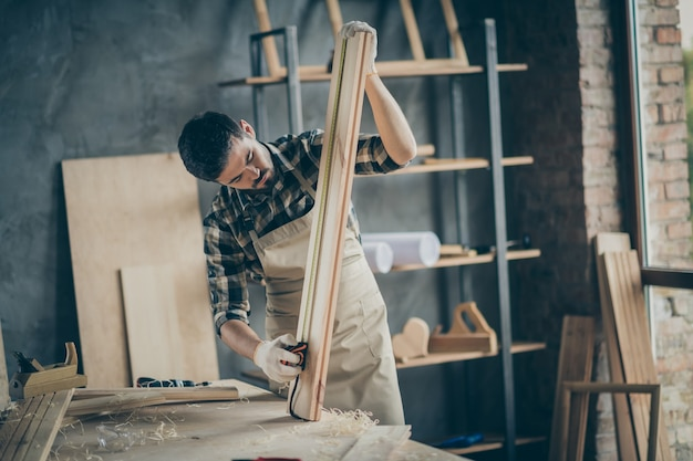 Portrait of his he nice attractive focused concentrated professional experienced guy expert carving wood creating cabinetry house project at modern industrial loft brick style interior indoors