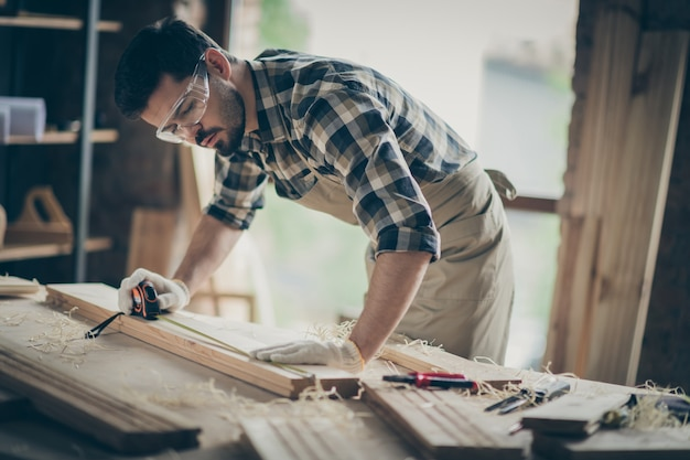Portrait of his he nice attractive focused concentrated professional experienced guy specialist carving wood creating new furniture project at modern industrial loft brick style interior indoors