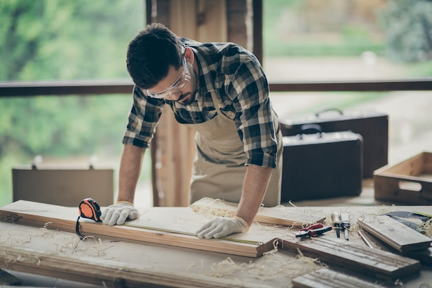 Portrait of his he nice attractive focused concentrated skilled experienced guy builder carving wood creating new cabinetry furniture at modern industrial loft brick style interior indoors