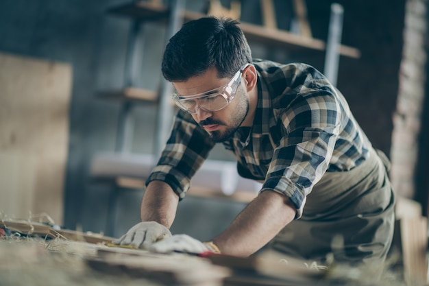 Portrait of his he nice attractive focused concentrated skilled experienced hardworking guy builder carving wood creating furniture at modern industrial loft brick style interior indoors