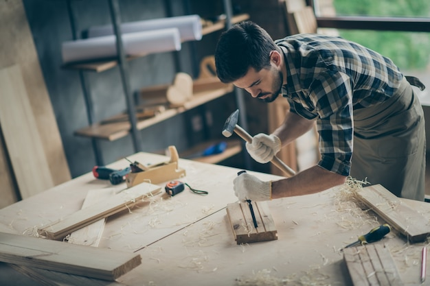 Portrait of his he nice attractive focused professional guy specialist creating start-up new modern home house decorative decor design thing order using hammer at modern industrial loft style interior