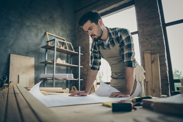 Portrait of his he nice attractive focused skilled hardworking guy making creating plan strategy developing building project at home modern industrial loft brick style interior indoors