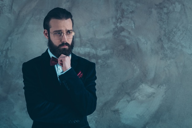 Portrait of his he nice attractive gloomy sad sullen bearded guy wearing tux thinking deciding isolated over gray concrete industrial wall