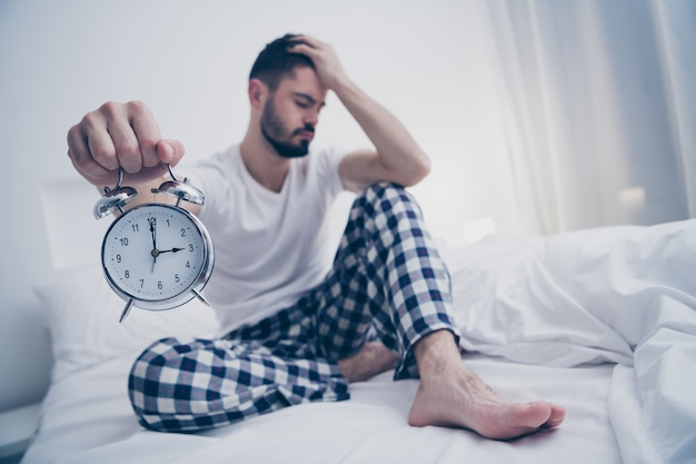 Portrait of his he nice attractive sad lazy tired bearded guy sitting on bed holding in hand alarm clock suffering at night late evening home dark room flat house indoors