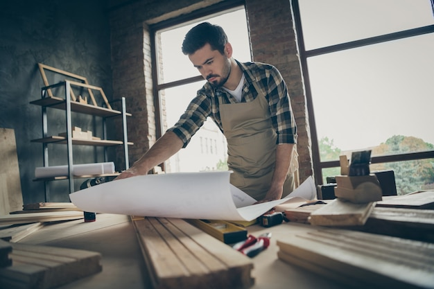 Portrait of his he nice attractive serious focused hardworking skilled experienced guy repairman reading plan new house building project at modern industrial loft style interior indoors