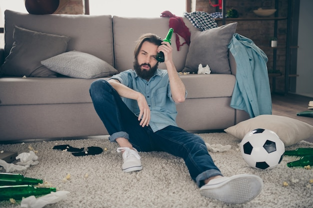 Portrait of his he nice attractive sick disappointed bearded guy sitting on floor suffering from pain early morning next day after party at industrial loft modern style interior room house indoors