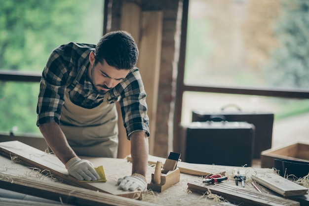 Portrait of his he nice attractive skilled hardworking professional guy self-employed builder carving wood on table desk making cabinetry at modern industrial loft brick style interior indoors