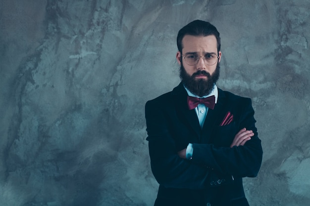 Portrait of his he nice attractive sullen puzzled bearded guy wearing tux folded arms isolated over gray concrete industrial wall