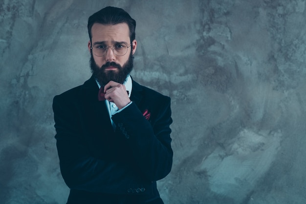 Portrait of his he nice attractive well-dressed sad bearded guy wearing tuxedo thinking isolated over gray concrete industrial wall
