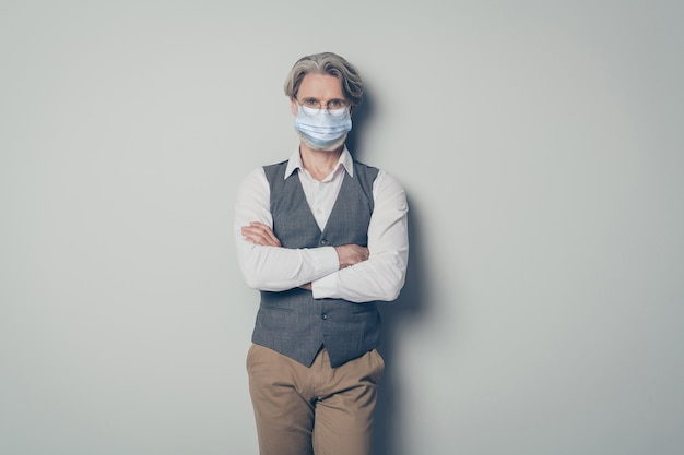 Portrait of his he nice healthy grey-haired man wearing safety gauze mask stop disease sickness illness mers cov novelty influenza pandemia prevention folded arms isolated gray color background