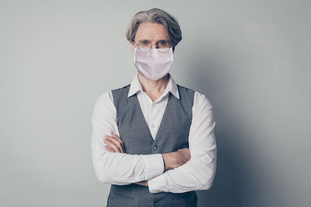Portrait of his he nice intelligent elderly grey-haired man retired pensioner wearing safety mask stop mers cov influenza pandemia stay home health care folded arms isolated gray color background
