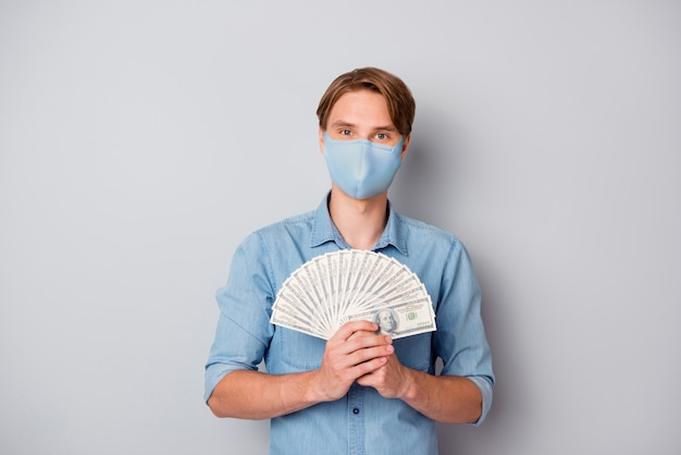 Portrait of his he nice rich attractive guy holding in hands fan cash million usd savings wearing safety reusable mask stop contamination stay home isolated over grey color background