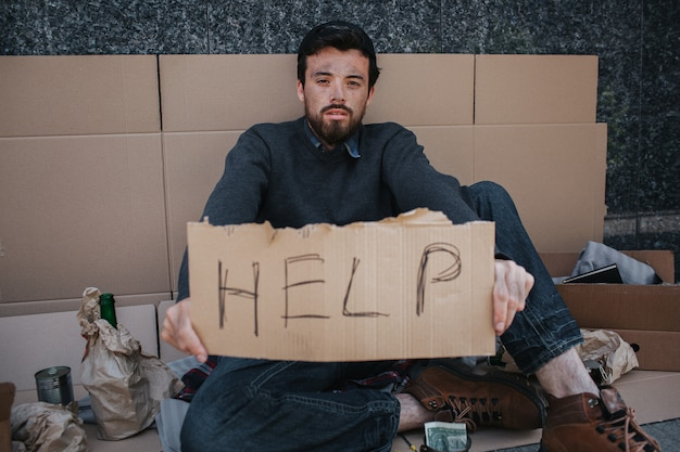 Portrait of homeless guy sitting on cardboard and holding a help cardboard in hands