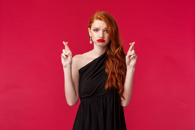 Portrait of hopeful worried caucasian female redhead in black luxurious dress, cross fingers good luck, want to win, making wish grimacing nervous, unconfident in own chances, red wall