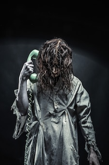 Portrait of the horror zombie girl calling by telephone. scary