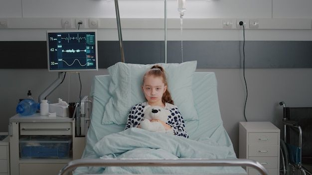 Portrait of hospitalized sick girl child patient holding teddy bear resting in bed during medical co...