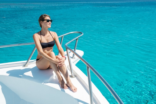 Portrait of hot attractive woman sitting on bow of yacht in bikini