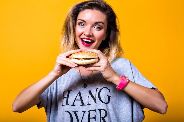 Портрет hppy смешная молодая стильная молодая женщина в серой футболке, выражая камеру
