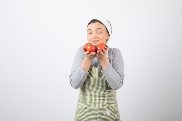 Il ritratto della donna affamata odora i pomodori rossi sopra il muro bianco