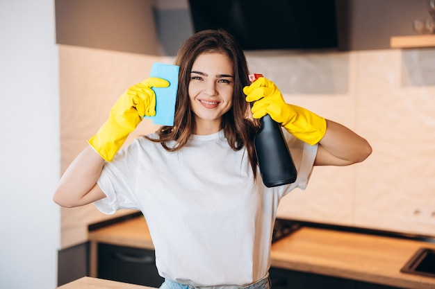Portrait of ice attractive playful housewife using spray having fun fighting killing dust struggling in modern light white interior kitchen house.