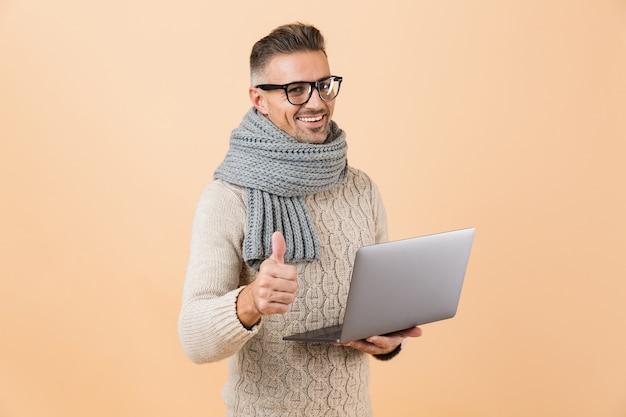 Портрет счастливого человека, одетого в свитер и шарф, стоящего изолированно над бежевой стеной, держащего портативный компьютер и показывающего большие пальцы руки вверх