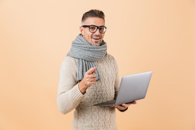 Портрет счастливого человека, одетого в свитер и шарф, стоящего изолированно над бежевой стеной, держащего портативный компьютер и указывающего пальцем