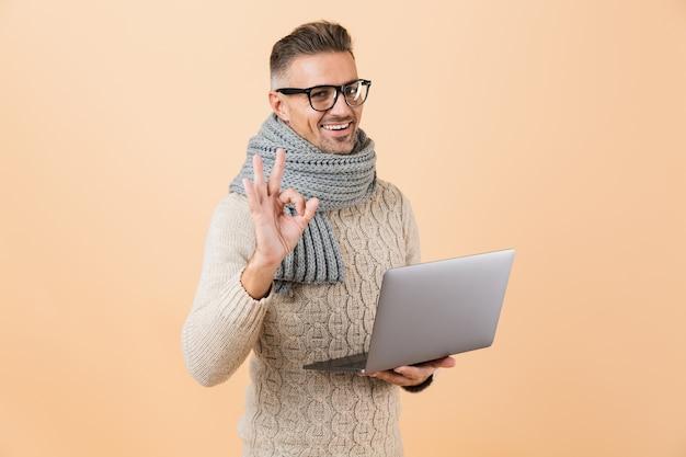 Портрет счастливого человека, одетого в свитер и шарф, стоящего изолированно над бежевой стеной и держащего портативный компьютер, показывая хорошо