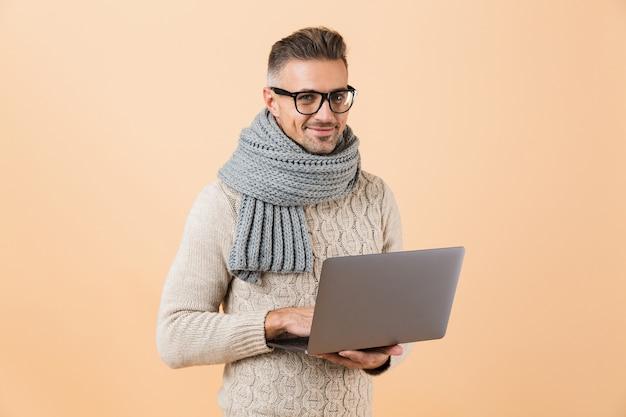 Портрет счастливого человека, одетого в свитер и шарф, стоящего изолированно над бежевой стеной и держащего портативный компьютер