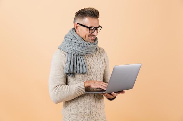 Портрет счастливого человека, одетого в свитер и шарф, стоящего изолированно над бежевой стеной и работающего на портативном компьютере