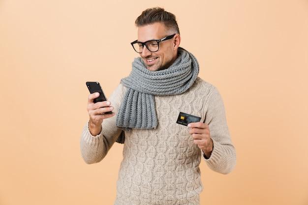 Портрет улыбающегося человека, одетого в свитер и шарф, стоящего изолированно над бежевой стеной, держащего мобильный телефон и показывающего кредитную карту