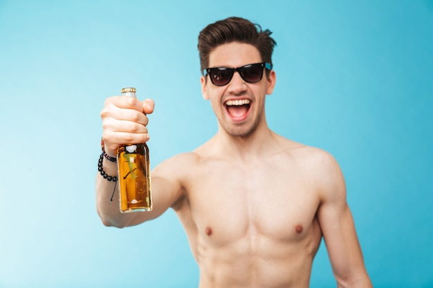 Portrait if a cheerful shirtless man showing beer bottle