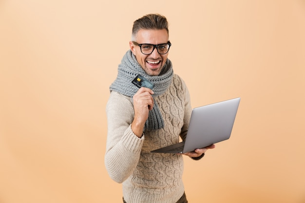 Portrait if a happy man dressed in sweater and scarf standing isolated over beige wall, holding laptop computer, showing plastic credit card