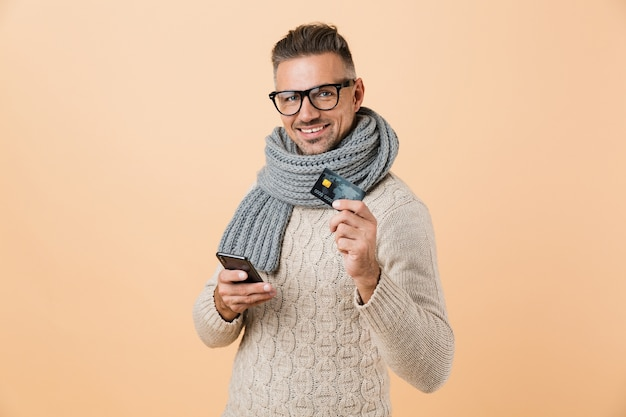 Portrait if a happy man dressed in sweater and scarf standing isolated over beige wall, holding mobile phone, showing credit card