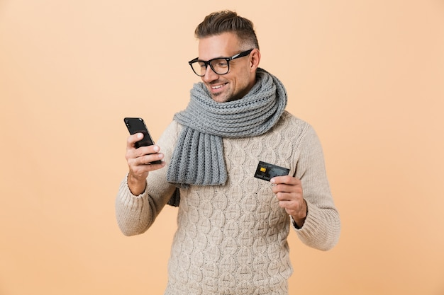Portrait if a smiling man dressed in sweater and scarf standing isolated over beige wall, holding mobile phone, showing credit card