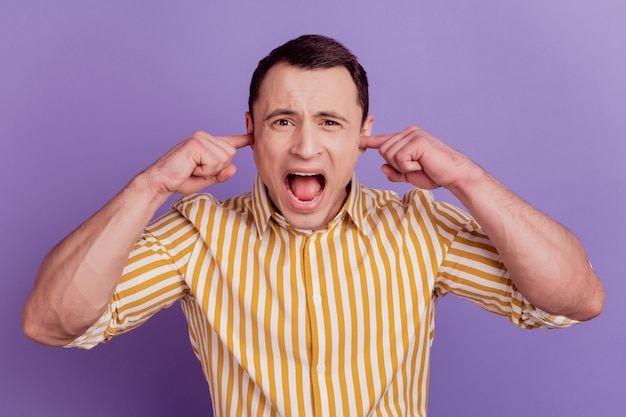 Portrait of ignoring crazy mad guy fingers close ears yell open mouth on violet background