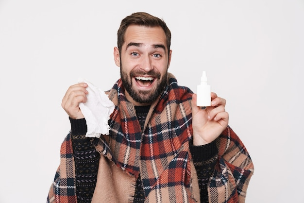 Portrait of ill caucasian guy wrapped in blanket sneezing and holding nose drops due to flu isolated over white wall