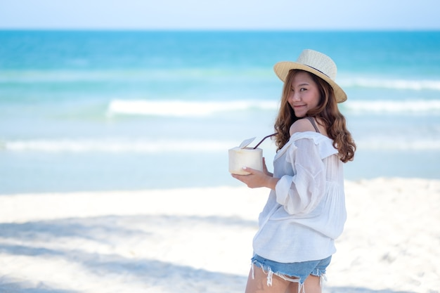 Portrait image of a beautiful asian woman holding and drinking coconut juice on the beach