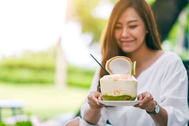 Portrait image of a beautiful asian woman holding and drinking coconut juice in the outdoors