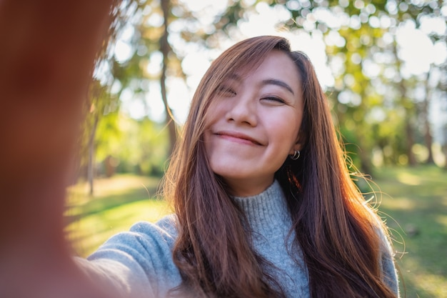 Portrait image of a happy beautiful asian woman making selfie photo in park