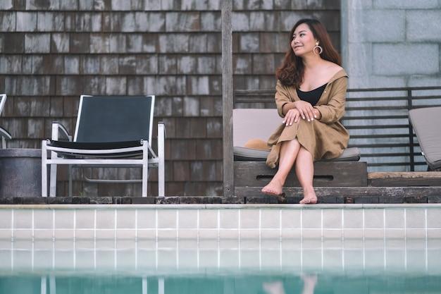 スイミングプールのそばに座って楽しんだ美しいアジアの女性の肖像画の画像