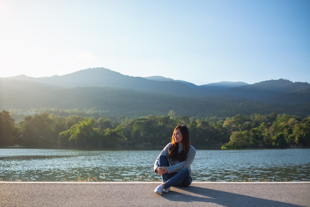 Портретное изображение красивой азиатской женщины, сидящей перед озером и горами перед закатом