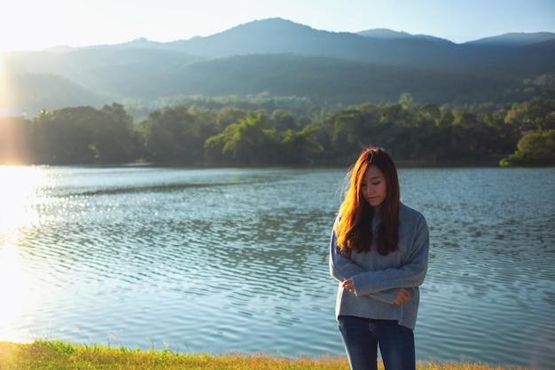 Портретное изображение красивой азиатской женщины, стоящей в одиночестве перед озером и горами в солнечный день