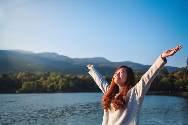 Портретное изображение красивой азиатской женщины, стоящей и раскрывающей руки перед озером и горами в солнечный день