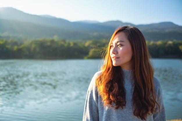 Портретное изображение красивой азиатской женщины, стоящей перед озером и горами перед закатом
