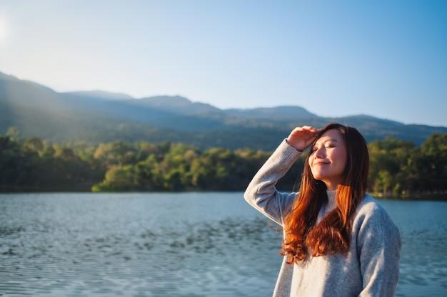 Портретное изображение красивой азиатской женщины, стоящей перед озером и горами в солнечный день