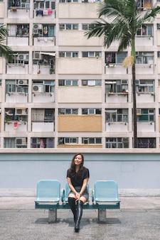 홍콩에 있는 빈티지 스타일의 파스텔 색상 건물을 가진 아름다운 아시아 여성의 초상화