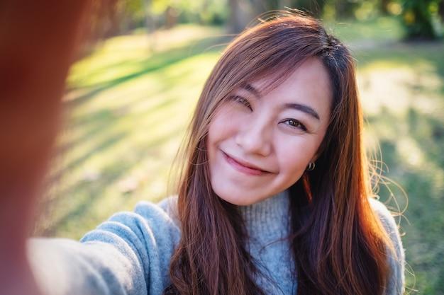 Портретное изображение счастливой красивой азиатской женщины, делающей селфи фото в парке