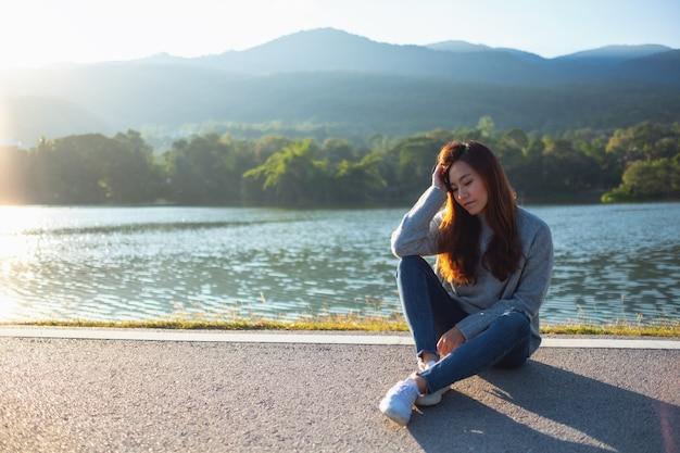 Портретное изображение грустной женщины, сидящей перед озером и горами перед закатом