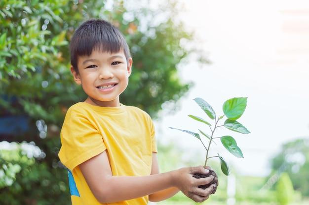 흙과 작은 녹색 식물을 들고 아시아 아이 소년의 초상화 이미지. 성장하는 나무. 봄 기간. 환경을 저장하십시오. 지구의 날. 세계의 날. 7 ~ 8 세.