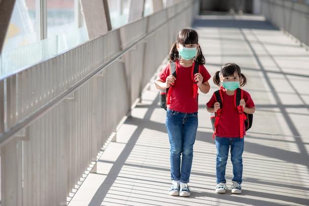 얼굴 마스크를 쓰고 학교 가방을 들고 다니는 작고 귀여운 아시아 어린이 형제들의 초상화. 다시 학교와 아이들에게. 어린 시절